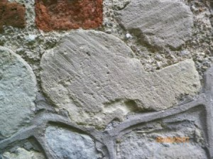 """Whistle stone"" reused in wall of cottage"
