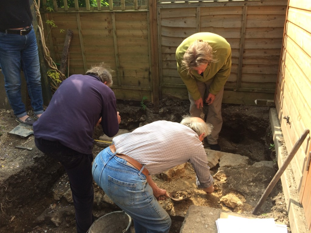 Dr John Crook and Hyde900 chairman Steve Marper continue the excavation as householder Chris Prior looks on