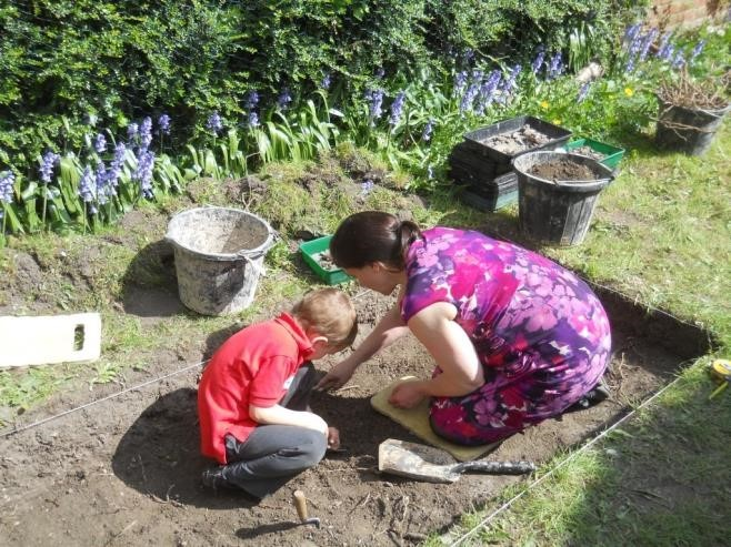 Pupil from St Bede's school digging trench 1 in householder Justine Field's garden