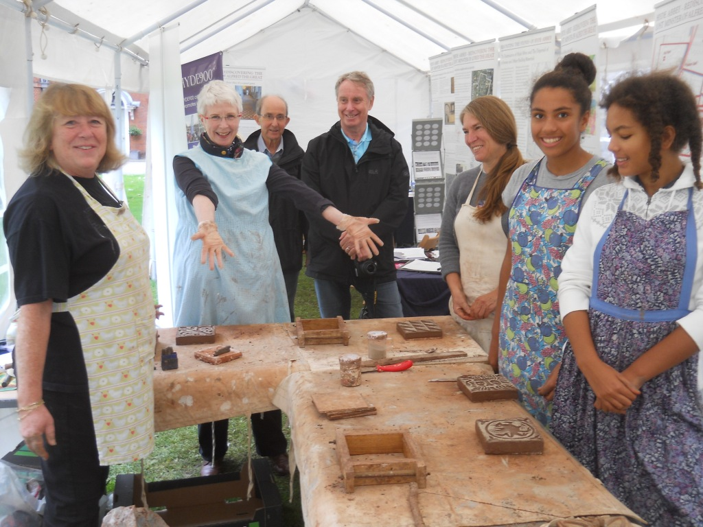 Delighted tilemakers admire their handiwork after instruction from Hyde900 trustee Rose Burns